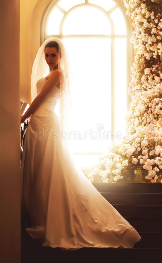 Bride on stairs near archwindow with roses stock photography