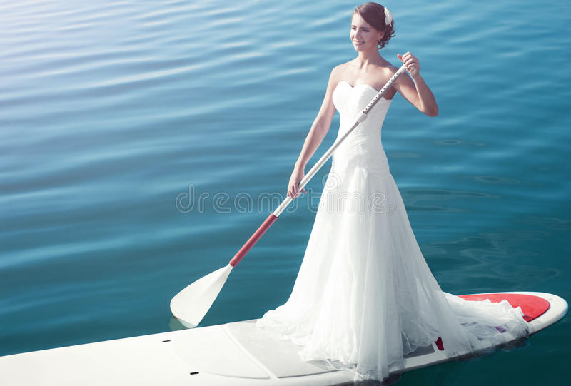 Bride stand up paddleboard stock image