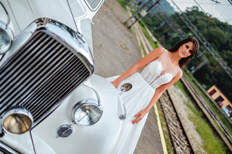 Bride standing by the classic car stock image
