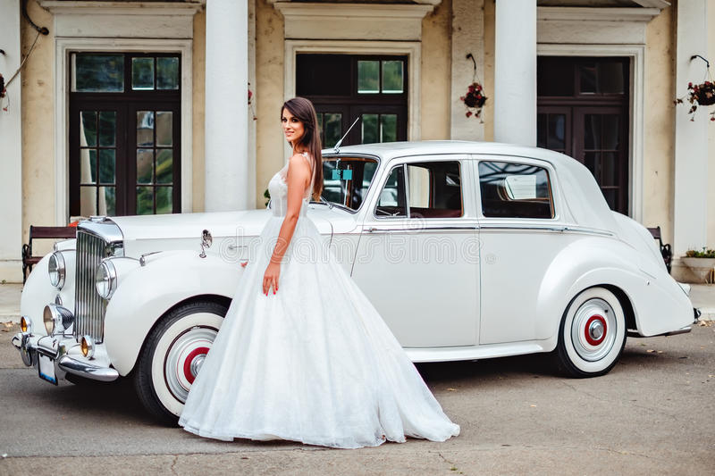 Bride standing by the classic car and smiling royalty free stock photos