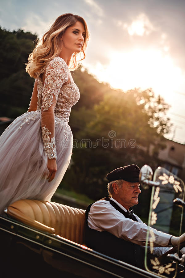 Bride standing proud in a classic convertible royalty free stock photo