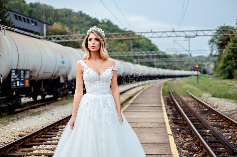 Bride standing by railroad tracks royalty free stock photo