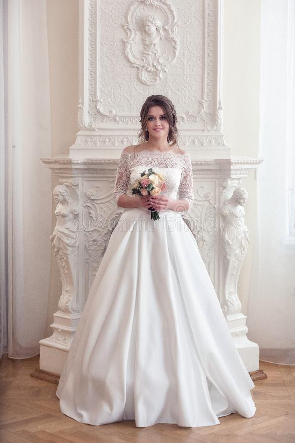 The bride stands near a large fireplace stock photos