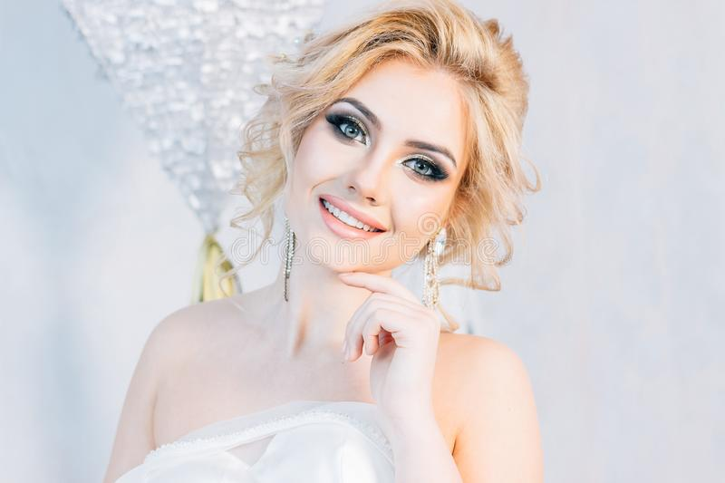 Beautiful blonde girl with beautiful make-up and hairstyle posin. The bride stands on a white wall background stock photography