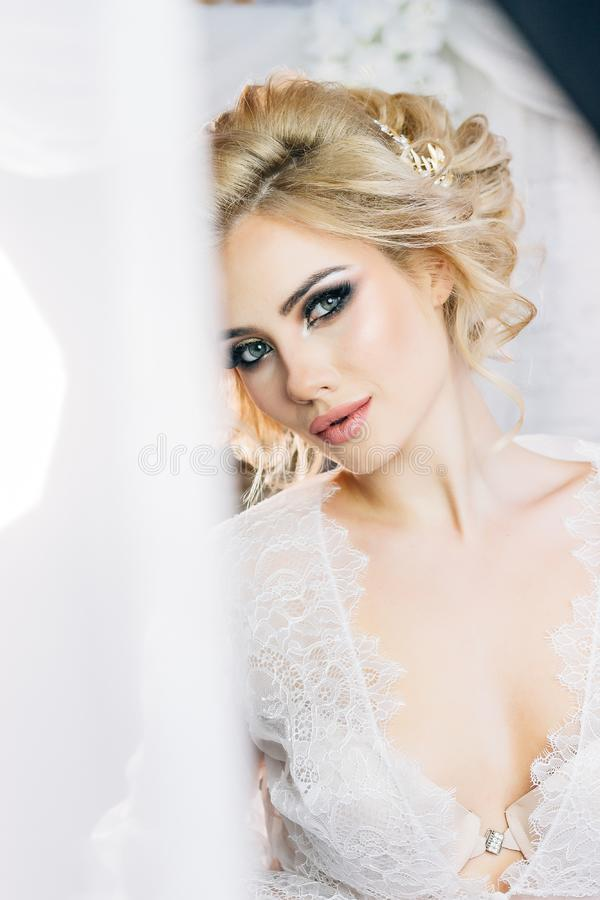 Beautiful model with expressive eyes and a sweet smile in a white negligee. The bride stands on a white wall background royalty free stock images