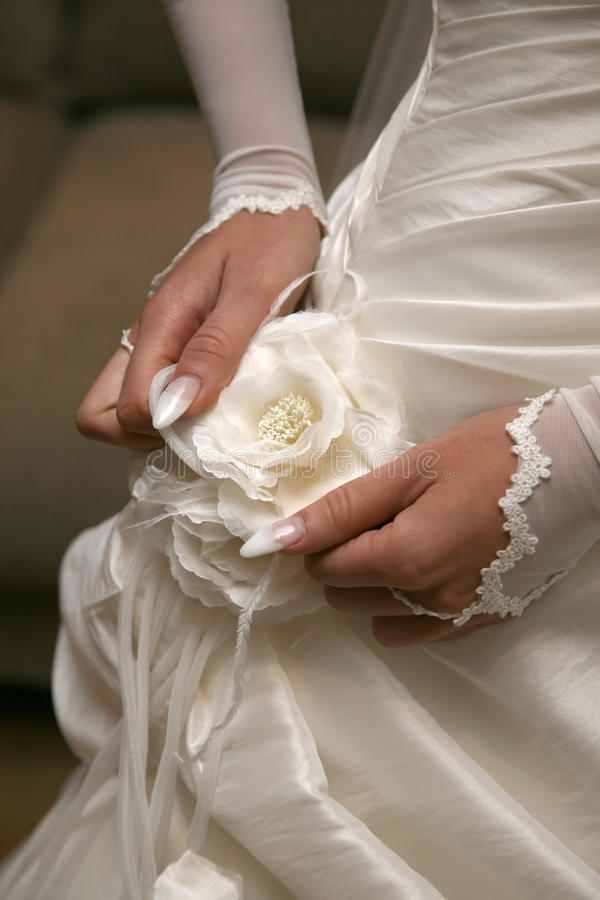 Bride straightens the flower on your dress. The bride straightens the flower on your dress royalty free stock image