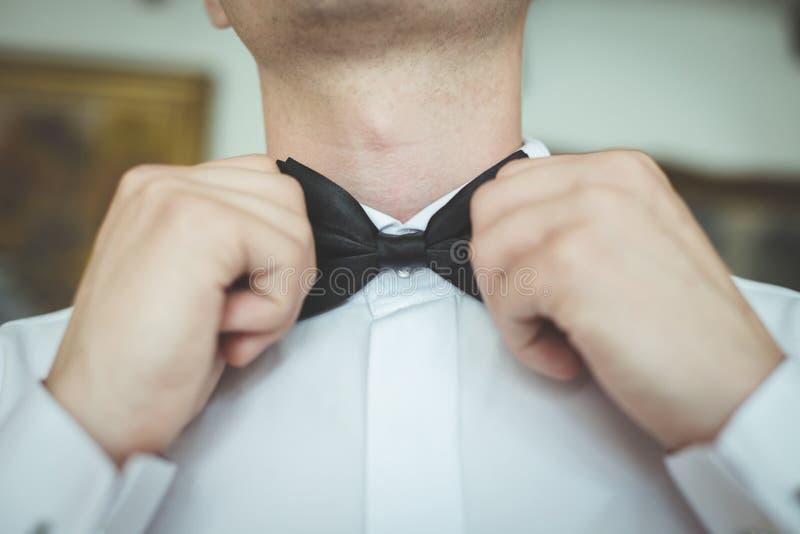 Bride straightens his tie. Bride preparing for the wedding and straightens his tie stock image