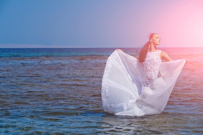 Bride on sunny summer day on blue water royalty free stock image
