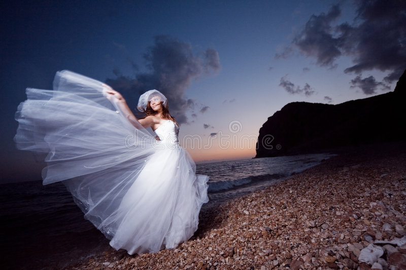 Bride on sunset beach. Bride posing showing her wedding dress on sunset beach