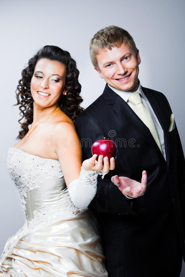 Bride tempting groom by red apple royalty free stock images