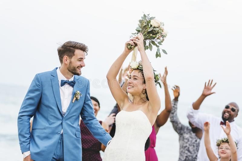 Bride throwing flower bouquet to guests stock images