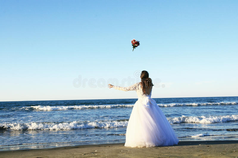 Bride throwing flowers stock photo