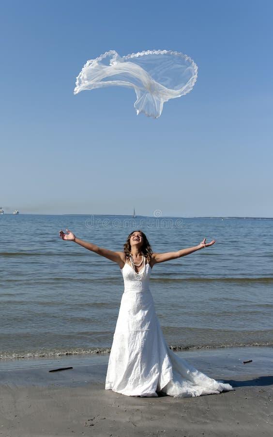 Bride throwing the veil near the sea. Beautiful young bride throwing the veil near the sea royalty free stock photo