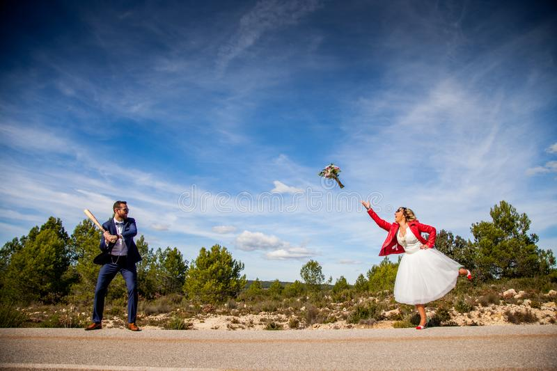 Bride throws her bouquet while groom prepares to hit him with a baseball bat royalty free stock photo