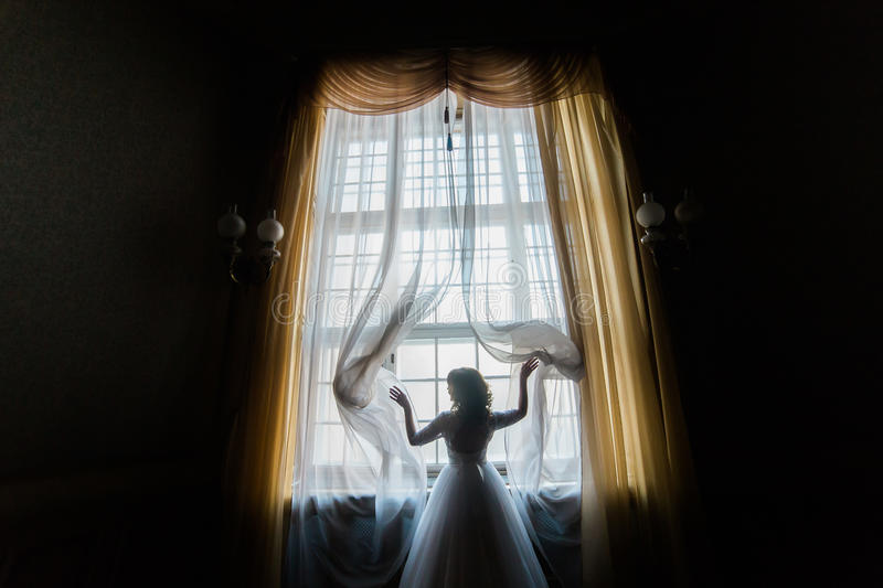 The bride touches the curtains while standing near the palace window. The horizontal back view. stock photography
