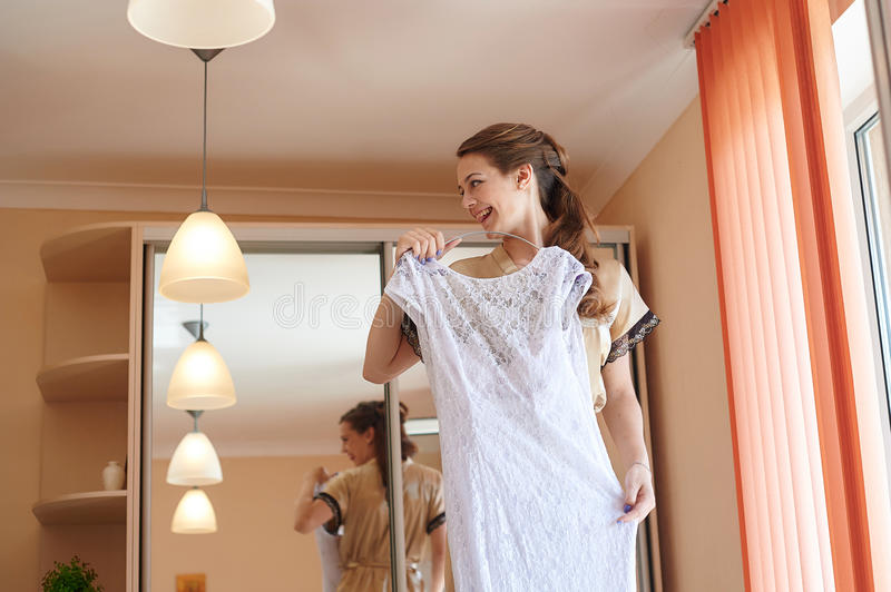 Bride trying on a dress in front of mirror in the wedding morning stock photo