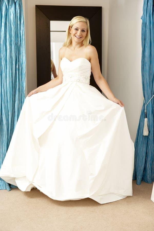 Bride trying on wedding dress stock photos