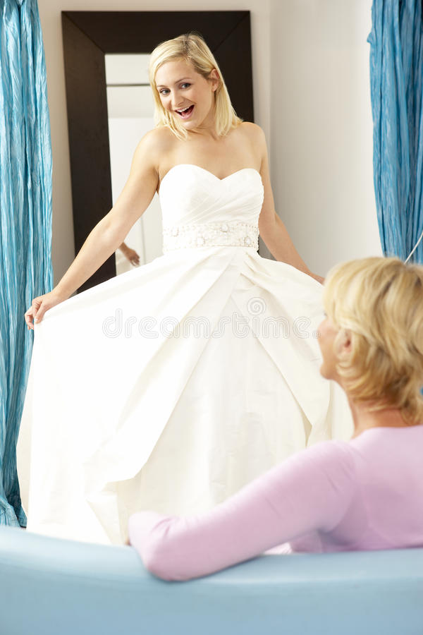Bride trying on wedding dress with sales assistant royalty free stock photography
