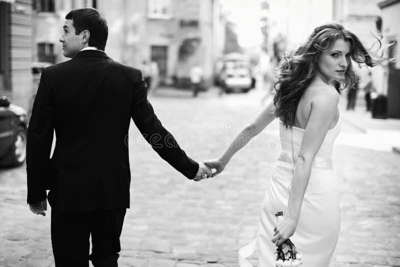 Bride turns around holding groom's hand while walking around the royalty free stock photo