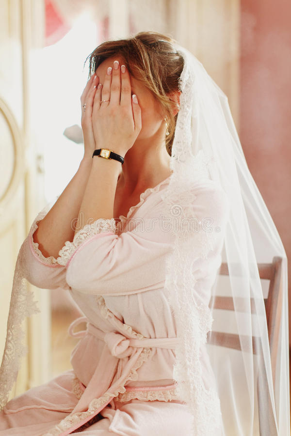 Bride in a veil sits on the chair and hides her face behind her stock photos