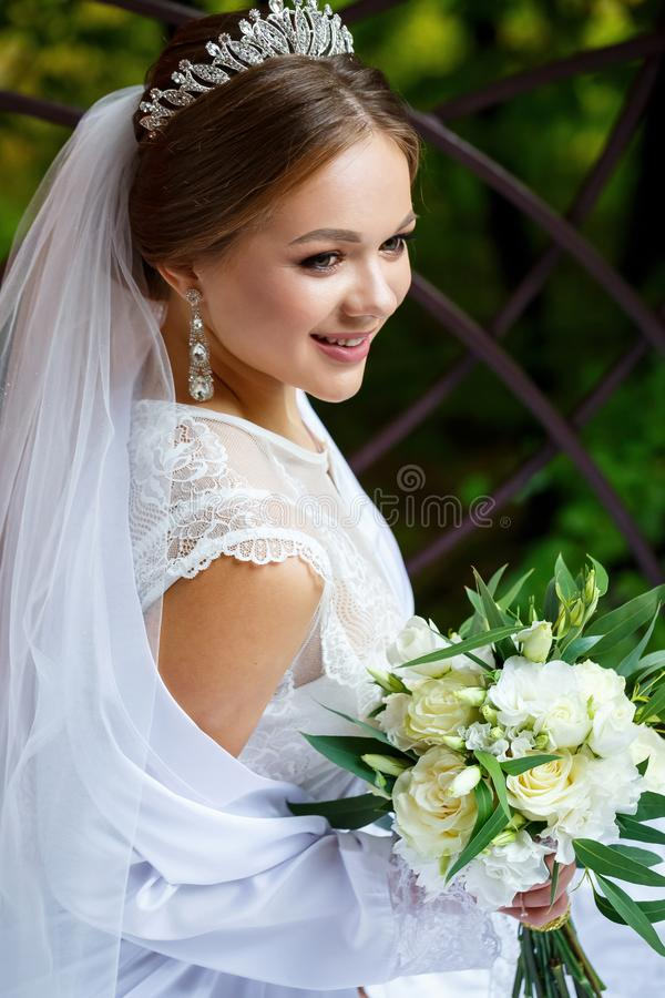Bride in veil and white coat sits on a blanket with a wedding bouquet in her hands royalty free stock photos