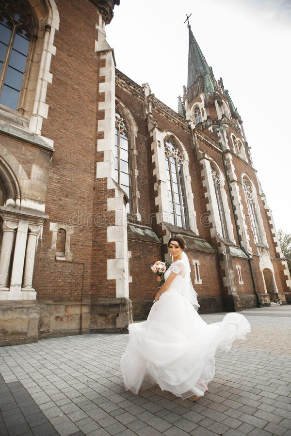The bride on a walk near the wall of old gothic church stock photos