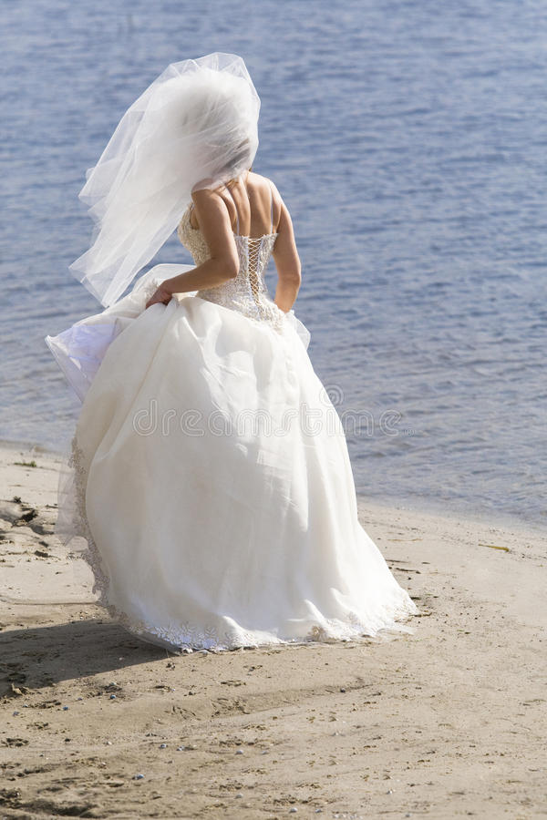 Bride walking on beach royalty free stock photos