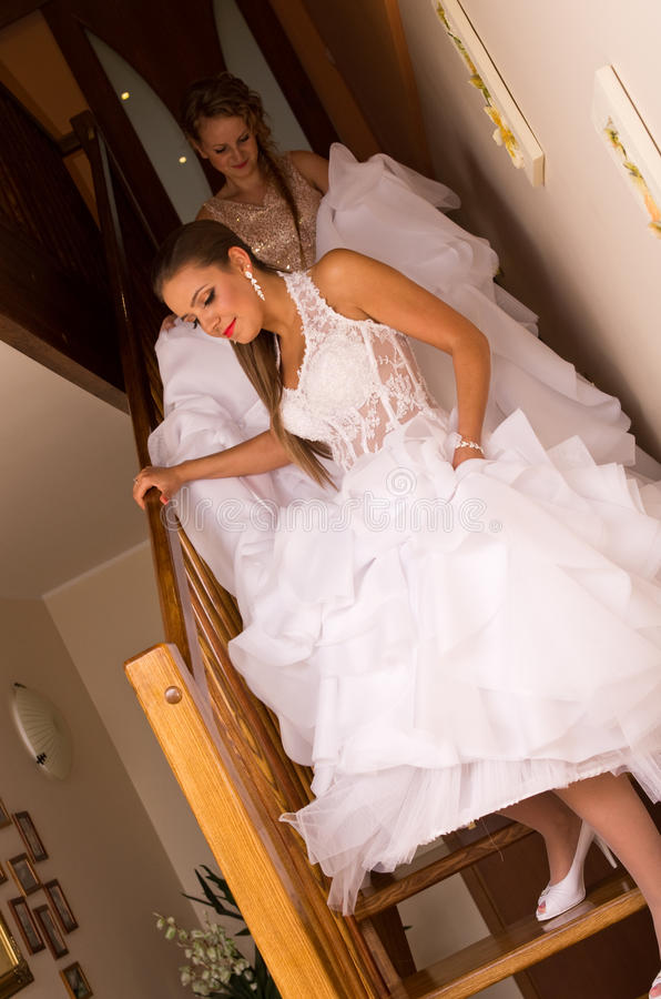 Bride walking down stairs stock image