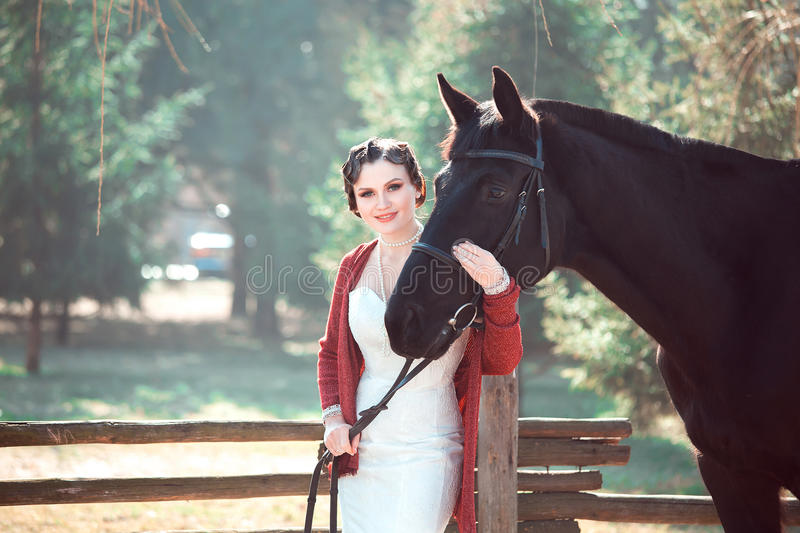 Bride walking with horses. Sincere feelings, a holiday for two, a wedding in retro style royalty free stock photos