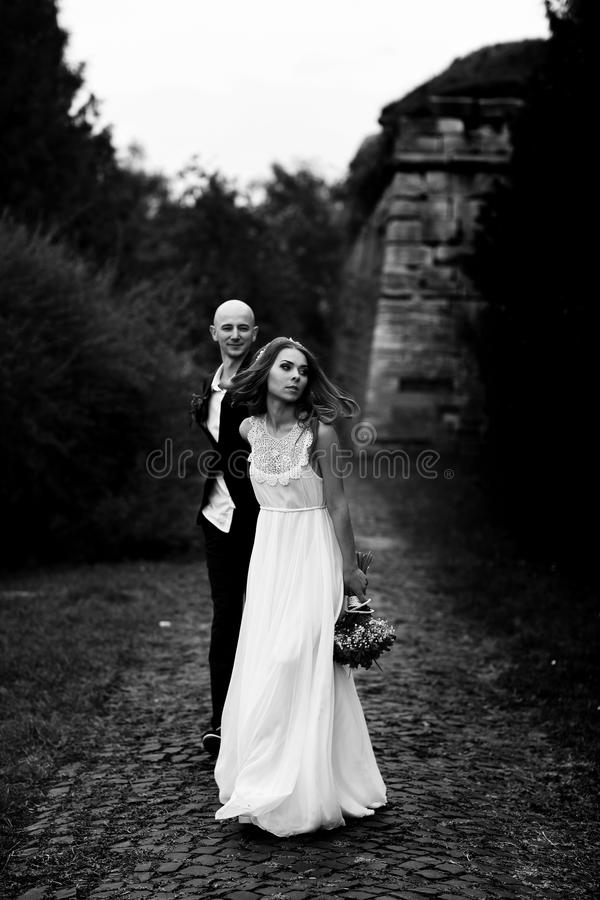 Bride walks along the pass in the park holding groom's hand stock photography