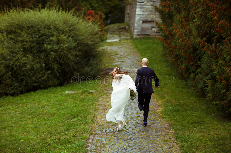 Bride waves holding dress in her arm while running with a groom stock image