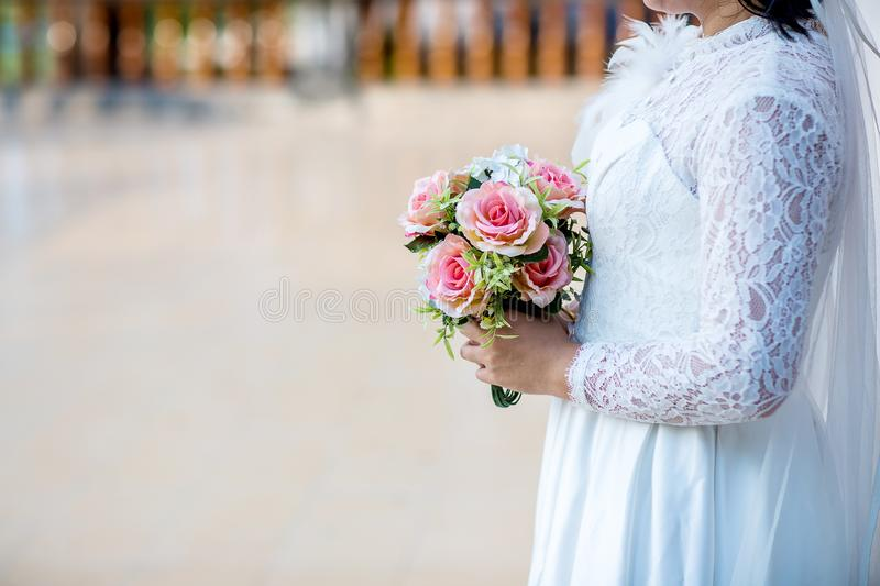 Bride wear white bride dress holding fresh beautiful flower bouquet. With blur background royalty free stock images