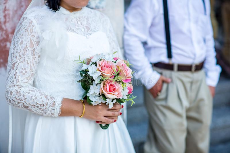Bride wear white bride dress holding fresh beautiful flower bouquet. With blur background stock photography