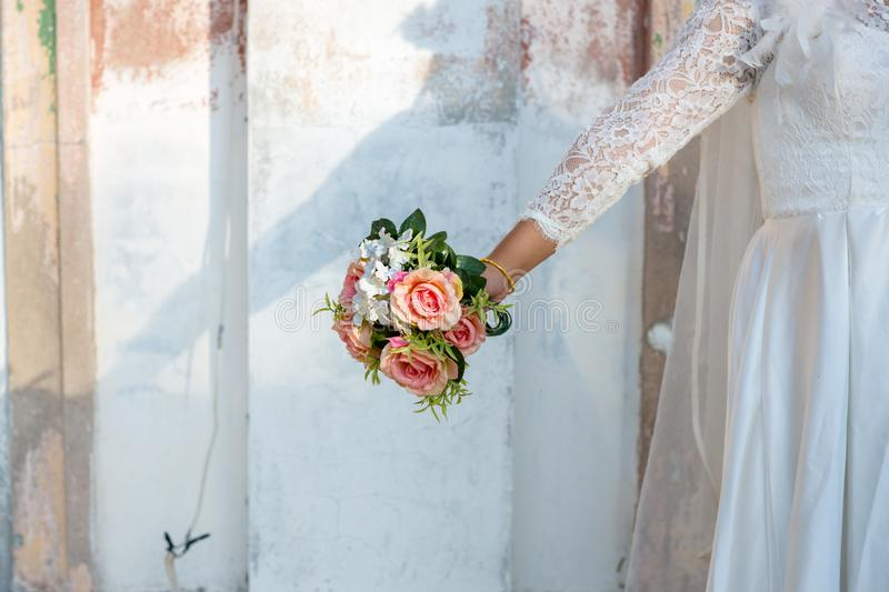 Bride wear white bride dress holding fresh beautiful flower. Bouquet with blur background royalty free stock photo