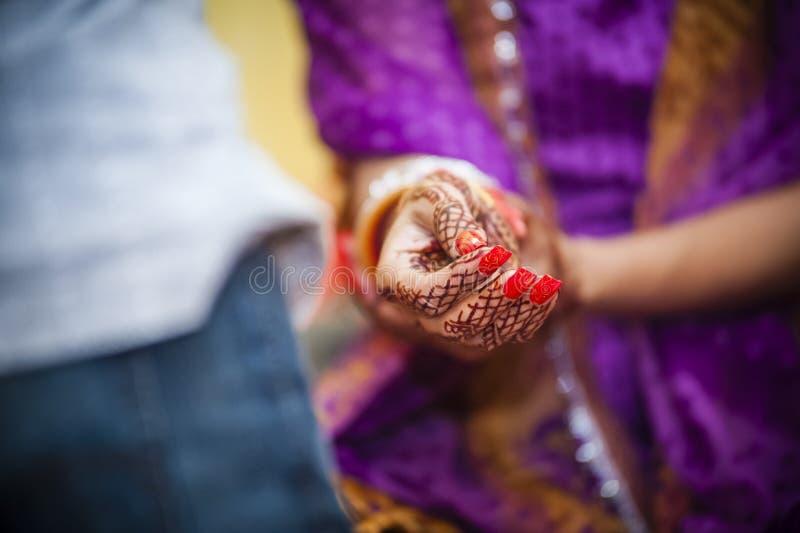 Bride wearing bangle bracelet. Punjabi bride's hands, fully decorated with henna decoration wearing bangle bracelet on her wedding day royalty free stock image