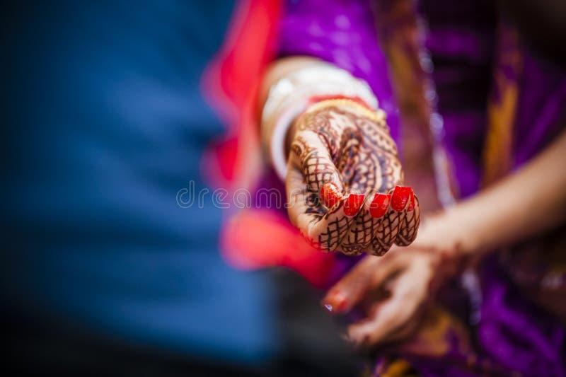 Bride wearing bangle bracelet. Punjabi bride's hands, fully decorated with henna decoration wearing bangle bracelet on her wedding day stock photography