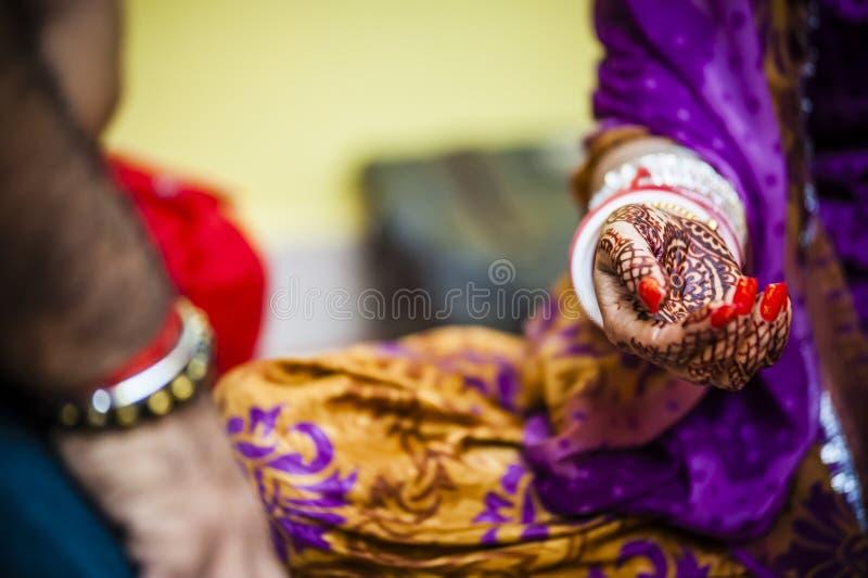 Bride wearing bangle bracelet. Punjabi bride's hands, fully decorated with henna decoration wearing bangle bracelet on her wedding day stock photo