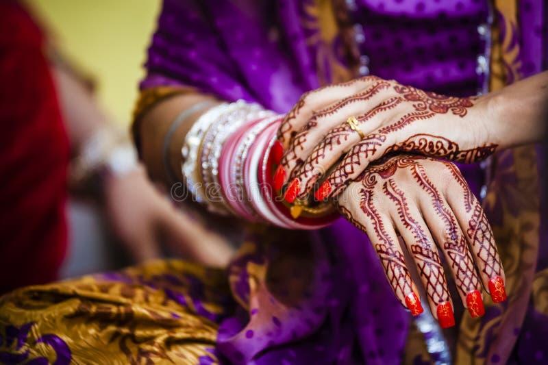Bride wearing bangle bracelet. Punjabi bride's hands, fully decorated with henna decoration wearing bangle bracelet on her wedding day stock photos