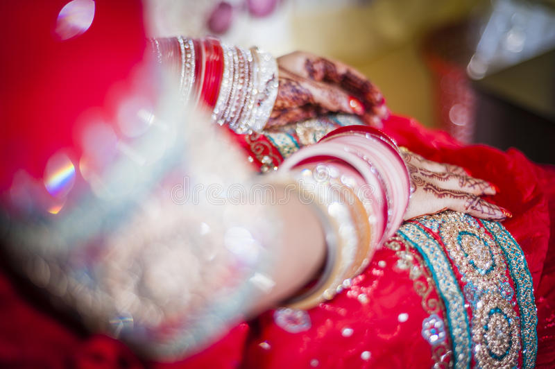 Bride wearing bangle bracelet. Punjabi bride's hands, fully decorated with henna decoration wearing bangle bracelet on her wedding day royalty free stock photography
