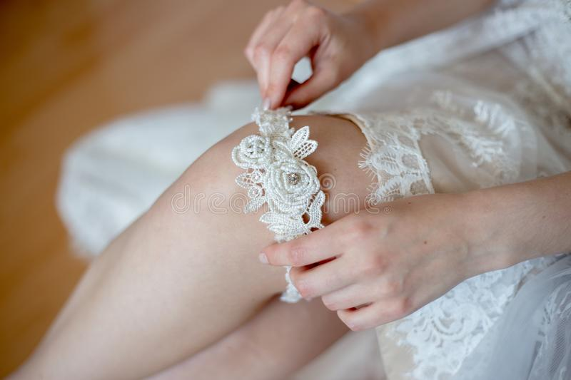 The bride is wearing a garter. Wedding preparations, the bride is wearing a garter royalty free stock photography