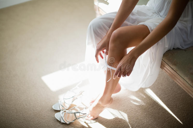 Bride wearing stockings in living room stock images