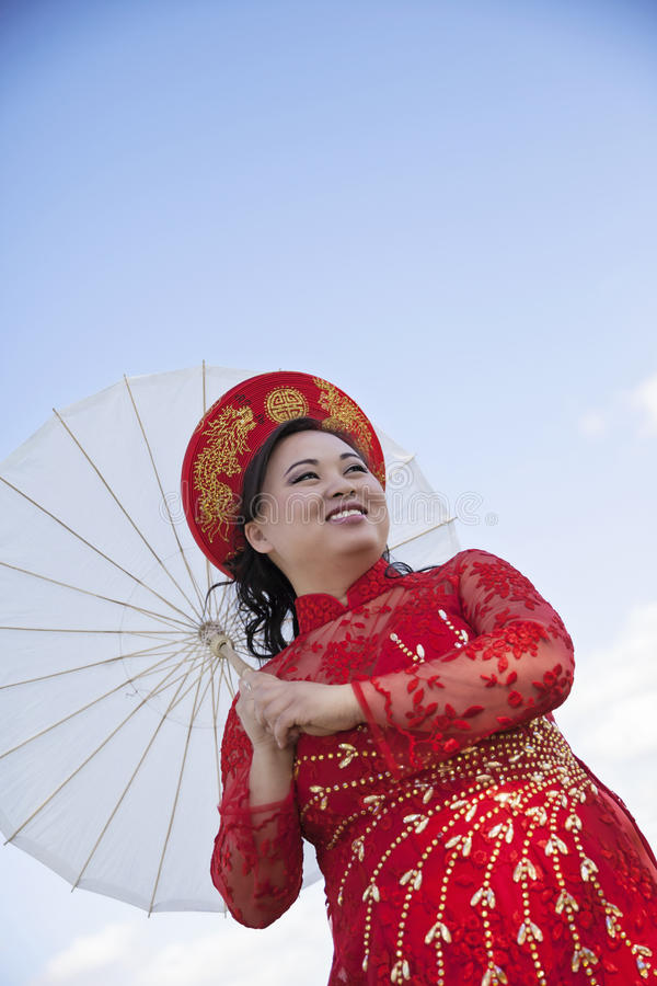 Bride wearing Vietnamese Ao Dai. Smiling woman wearing traditional Vietnamese Wedding dress Ao Dai with hat and parasol