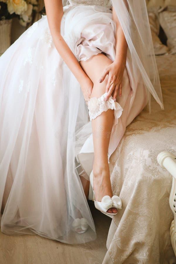 Bride wearing wedding garter. Hands stock photos