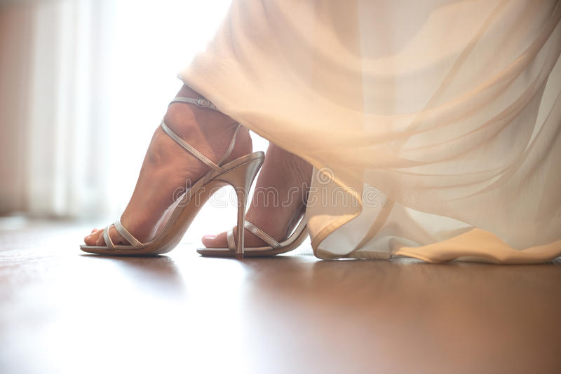 Bride wearing wedding shoes. Close-up details of brides feet wearing shoes royalty free stock image