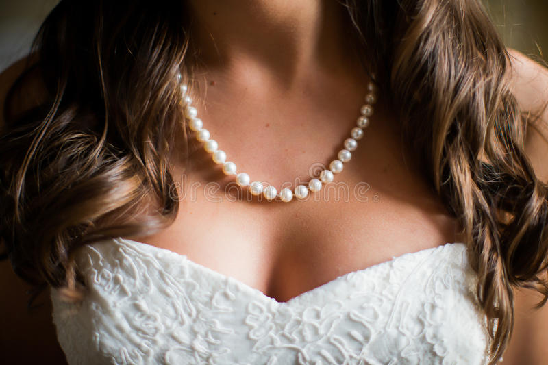 Bride wearing white pearl necklace. Closeup of bride wearing white pearl necklace royalty free stock image
