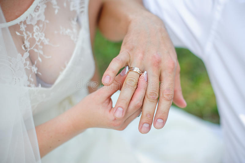 Bride Wears A Gold Wedding Ring On The Finger Of The Groom Stock