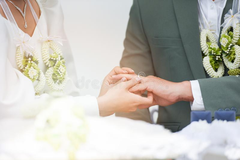 The bride wears a wedding ring on the groom left hand ring finger on her wedding day royalty free stock photos
