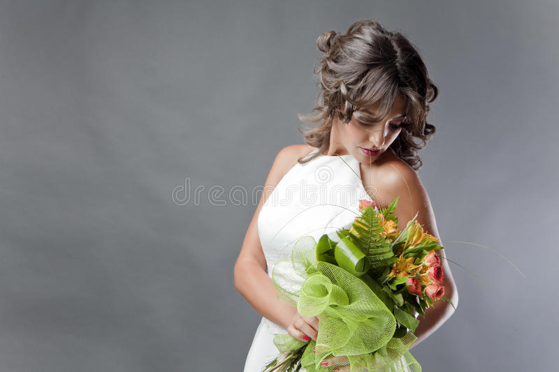 Bride with wedding bouquet. And white wedding dress on studio background stock photography