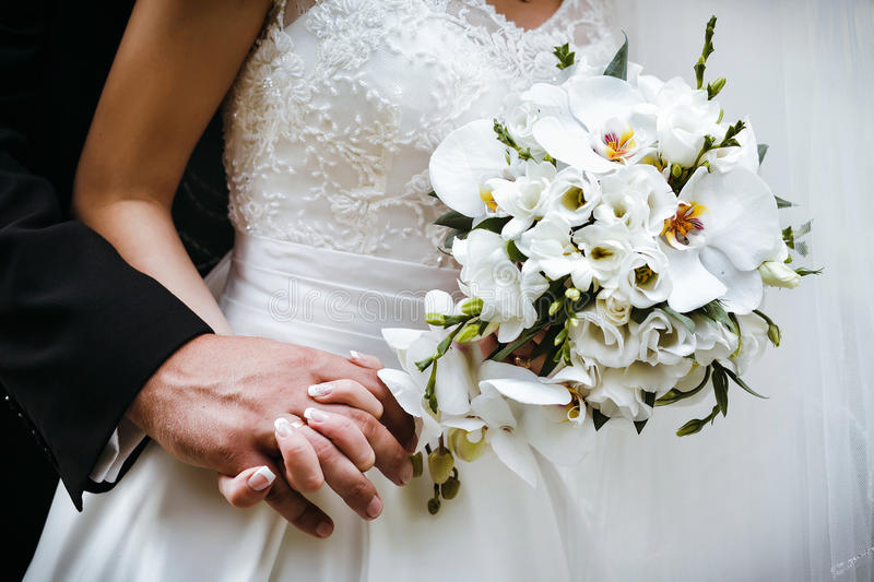 Bride with wedding bouquet of white orchids and groom holding ea. Ch others hands stock photography