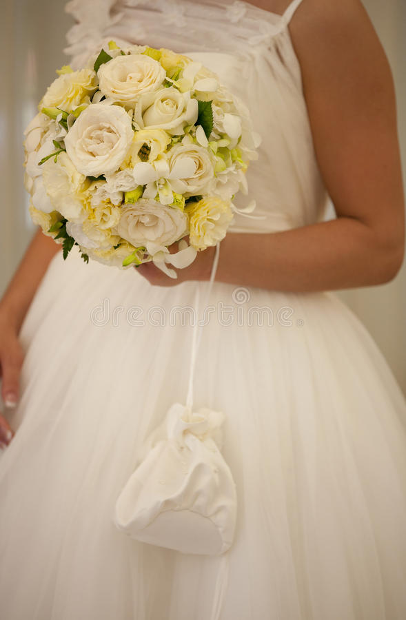 Bride with wedding bouquet of white and yellow roses, silk bag with pearls ang strings royalty free stock images